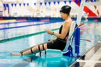 a paraplegic woman is lowered into the swimming pool on a lift and prepares to swim, edmonton, alberta, canada