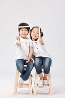 Boy and girl holding a frame sitting on stools