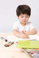 Boy coloring with crayons