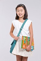 Girl wearing school bag holding book