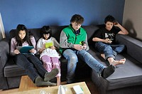 Four Swedish kids, two sisters and two brothers, ages 10 and 14, playing games on each otheir own tablets, digital tablet, smartphone, iPod and Ninten...