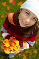Teen girl holds handful of colorful autumn leaves