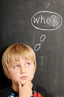 Stock photo of a young boy in fornt of a blackboard with chalk thought bubbles spelling the word WHO
