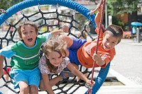 Children playing on a large net swing on playground