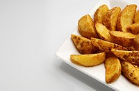 forefront of a fried potato slices on a white plate