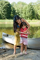 Mother putting lifejacket on daughter