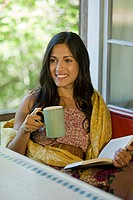 Woman relaxing with a drink and a book (thumbnail)
