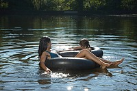 Mother and daughter in lake on inflatable rings