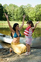 Mother and daughter by rowboat with raised arms