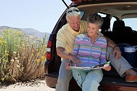 Mature couple sitting on boot of car with map