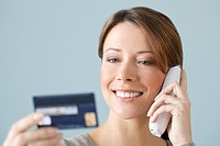 Young woman on the phone with credit card