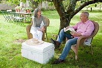 Mature couple outdoors, man reading book