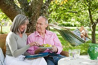 Mature couple eating from plate of food