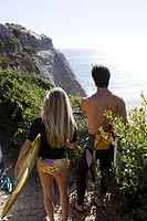 Young couple near the sea with surfboards