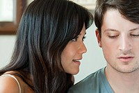 Young woman looking closely at boyfriend (thumbnail)