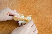 Person wrapping small gift