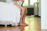 Legs of woman on bed with tissue box