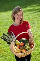 Young woman holding a fruit basket