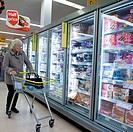 A woman with a trolley shopping for food in a branch of the Co-op supermarket, UK