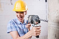 Laughing craftswoman with hard hat and power drill