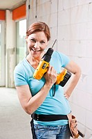 Smiling woman with cordless screwdriver