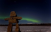 Inuit stone man, inukshuk, stone landmark or cairn, Northern Polar Lights, Aurora Borealis, green, near Whitehorse, Yukon Territory, Canada