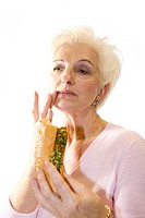 A woman with a sausage in a baguette in her hand wipes off her mouth