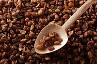 Dried raisins, sultanas, Thompson Seedless, with an old wooden spoon