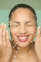 A smiling woman washing her face.