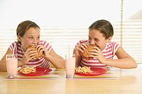 Twin teenage girls eating hamburgers.