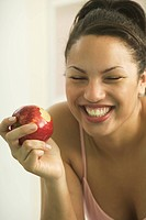 Young woman holding a red apple.