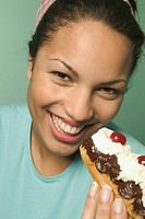 Young woman eating an eclair pastry.