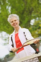A middle_aged woman playing tennis