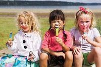 Girls eating frozen treats outdoors
