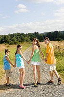 Family holding hands on country road