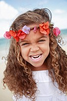 Hawaii, Oahu, Lanikai, Young girl wearing flower headband makes funny face at beach.