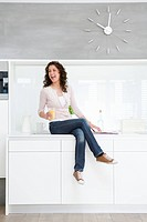 Woman sitting on kitchenette
