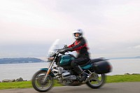 Woman riding motorcycle on coastal road