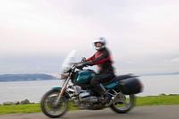 Woman riding motorcycle on coastal road