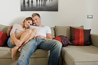 Young smiling couple relaxing on sofa