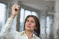 USA, New Jersey, Jersey City, Businesswoman writing calculations on glass