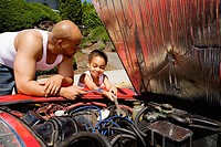 Young boy helping his father work on car