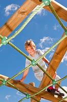 A  picture of a seven year old boy on a climbing frame in the Uk