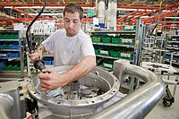 Operator working in the production of gearboxes for the automotive industry at the ZF Friedrichshafen AG, an automotive supplier, Friedrichshafen, Bad...