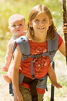 Girl carrying baby sibling on back