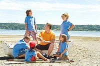 Male camp counselor and children at beach