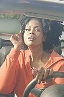 African woman applying mascara in car