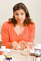 Woman holding handful of vitamins and supplements