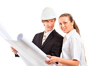 An architect wearing a hard hat and co_worker reviewing blueprints