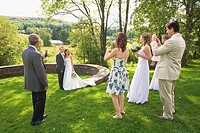 Group of people photographing a newlywed couple in a park, East Meredith, New York State, USA